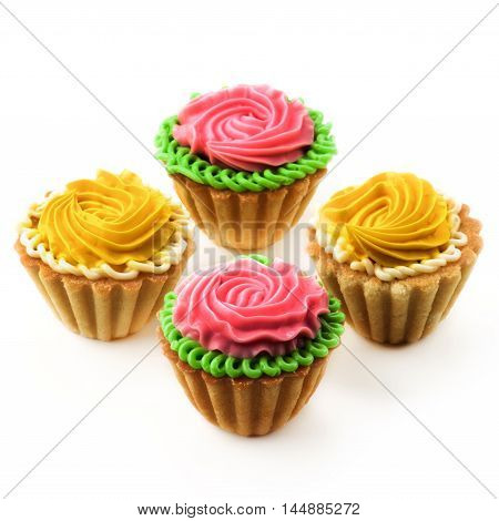 Arrangement of Delicious Little Tarts with Colored Butter Cream and Decoration closeup on White background