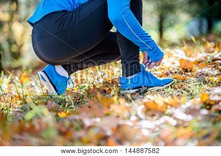 Unrecognizable Runner Sitting On The Ground, Tying Shoelaces, Au