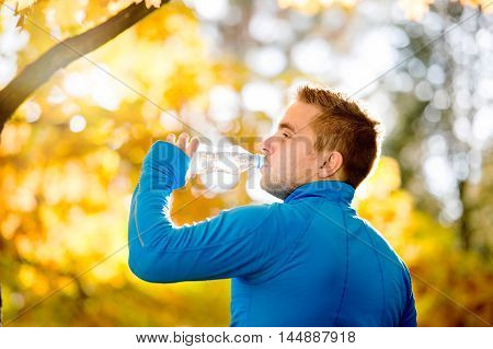 Hipster Runner In Autumn Nature Drinking Water From Bottle