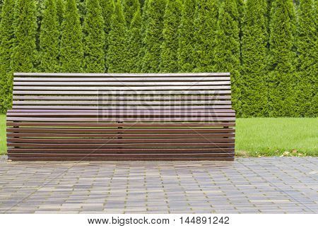 Modern stylish brown wooden bench outdoor furniture in the park as background image