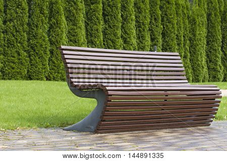 Modern stylish curve shaped brown wooden bench outdoor furniture in the park as background image