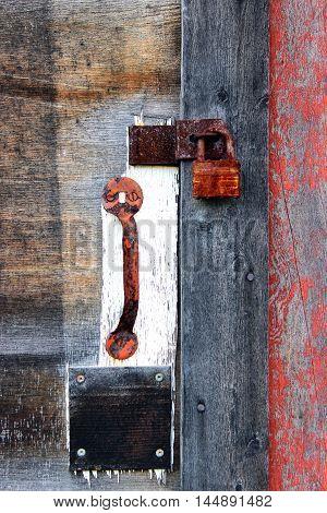 rusty old padlock and door handle attached to weathered wood door in disrepair closeup
