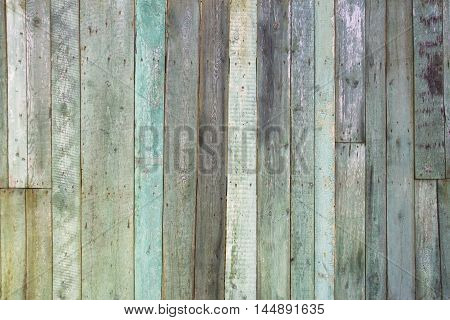 Old, grunge wood panels painted in turquoise color used as background.