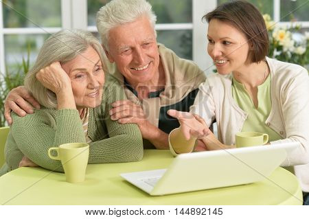 Senior couple portrait with laptop with caring daughter