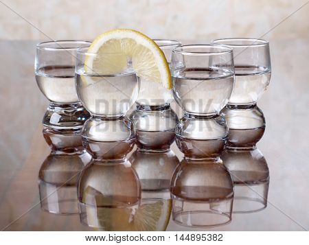 Glass with tequila and lemon on the table