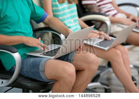 Young people with laptops hanging out together