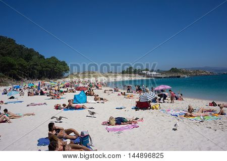 VIGO, SPAIN - AUGUST 18, 2016: Tourist on Rodas Beach on Cies Islands Natural Park off the coast of Vigo. With white sand and clear waters, Rodas Beach is half a mile long and 200 feet wide.