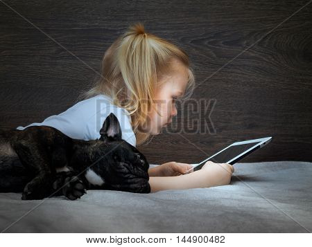 Little girl lies on a tablet and a dog bed