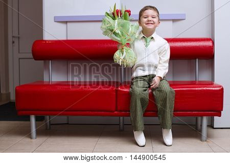 little boy with flowers bouquet sitting on couch