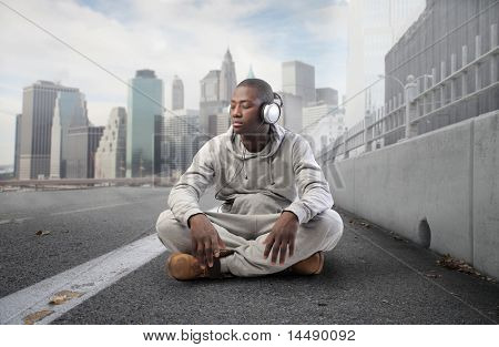 African young man listening to music on a city street