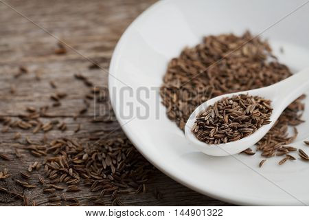 Cumin seeds or caraway in white spoon on wooden board.