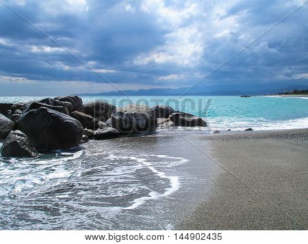 Coastline with rocks after a storm, black clouds and green sea.