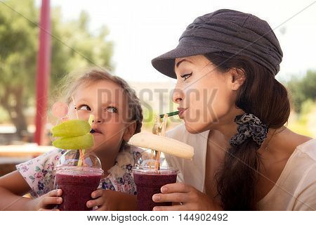 Happy Kid Girl And Funny Emotional Mother Drinking Berries Smoothie Juice Together In Street Cafe An