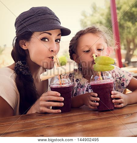 Happy Kid Girl And Funny Emotional Mother Drinking Berries Smoothie Juice Together In Street Cafe. C