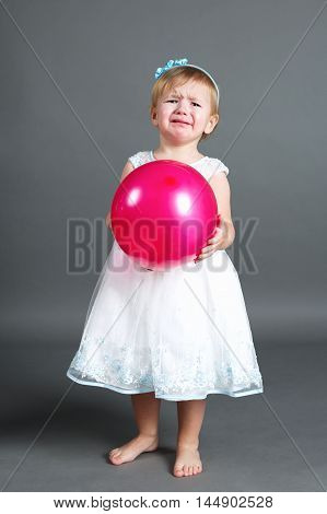 little sweet crying girl with pink balloon