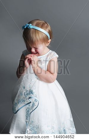 photo of cute little crying girl on dark background