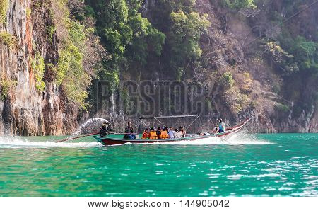 Suratthani Thailand - April 14 2015 : Travelling tourists travel by long trail boat with speed on green water surface for sight seeing nature in Thailand's dam.