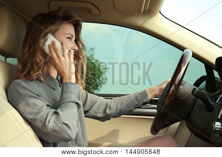 Pretty young woman using mobile phone while driving car