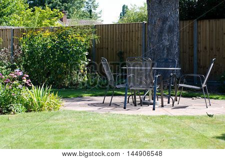 Patio with table and chairs in garden