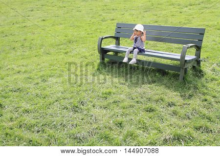 Japanese girl sitting on the bench in the field (1 year old)