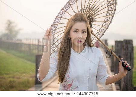 The Beautiful Burmese Woman In Myanmar Traditional Costume,with Umbrella Walking On Ubein Bridge, Ma