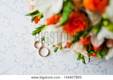 Wedding Bouquet With Rings On Vintage Table