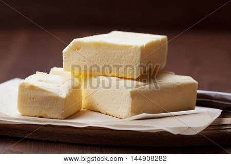 Stick of butter on wooden cutting board.