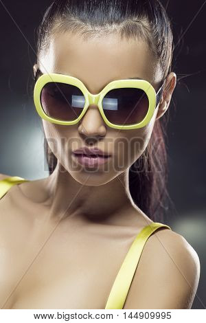 Beautiful model in yellow sunglasses studio shot