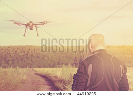 Silhouette of a man operating a drone with remote control for video shooting in a summer day. Sun filter. Toned image