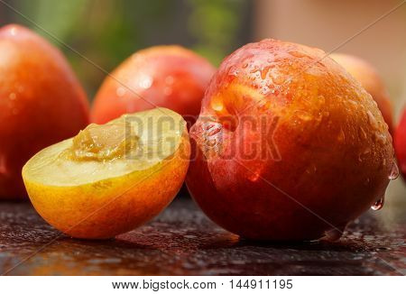 Sweet plums with waterdrops on a wooden table