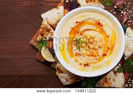 Hummus or houmous appetizer, made of mashed chickpeas with tahini, lemon, garlic, olive oil, parsley and paprika. Vegan superfood. Top view, copy space for text.