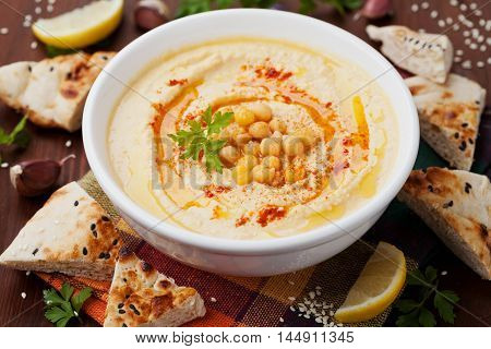 Hummus or houmous appetizer, made of mashed chickpeas with tahini, lemon, garlic, olive oil, parsley and paprika. Vegan superfood.