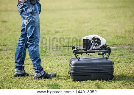 Drone on box near the men's feet on background of green grass