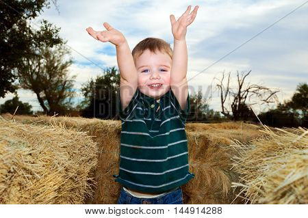 An excited little boy raises his hands in the air. He has found the end of a hay maze at a Fall festival.