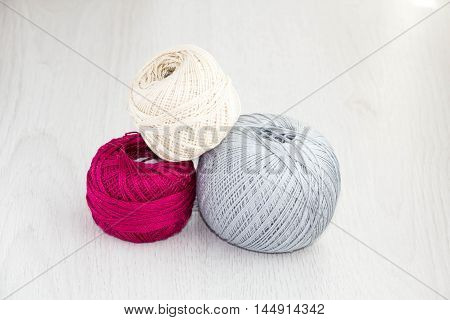 Crochet hooks and balls of yarn on wooden background with copy space Basket with hue knitting yarns hobby handmade tailor hand sewing and knitting theme design.