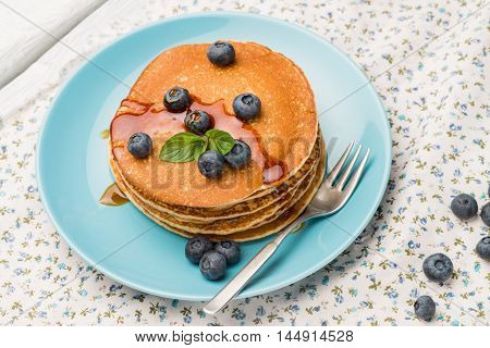 Closeup of delicious golden pancakes with fresh blackberries.