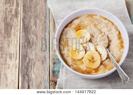 Bowl of oatmeal porridge with banana and caramel sauce on rustic table. Hot and healthy breakfast for every day. Diet and healthy food. Top view.