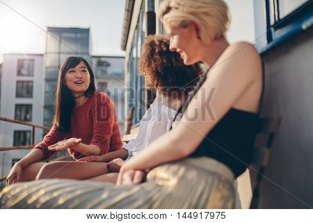 Multiracial Women Relaxing Outdoors In A Balcony