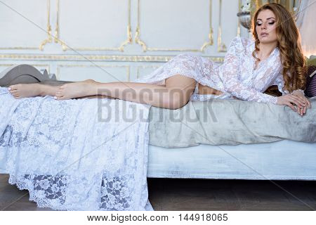 Beautiful Sexy Lady In Elegant White Robe. Close Up Fashion Portrait Of Model Indoors. Beauty Blonde