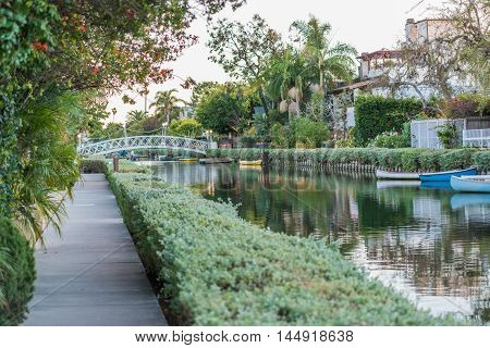 Venice, USA - December 25, 2015: Italian-like green canals in Los Angeles during evening sunset with canoes and bridge