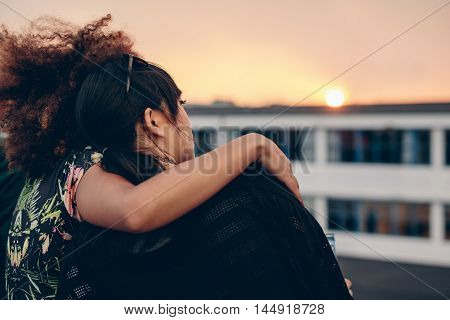 Rear view of young women relaxing on rooftop and looking at sunset.