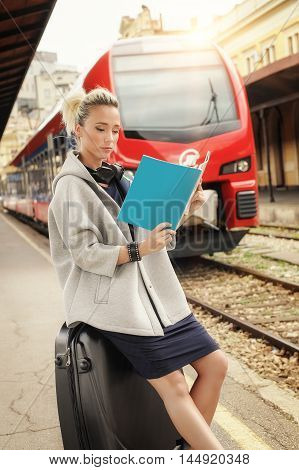 Young pretty woman reading a magazine at railway station platform