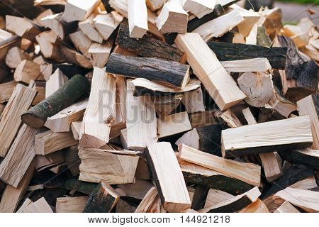 Firewood background - chopped firewoods on a stack