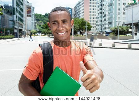 African american male student showing thumbs up in city outdoor in the city in the summer