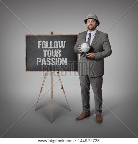 Follow your passion text on blackboard with businessman holding globe in hands