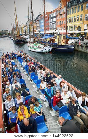 COPENHAGEN DENMARK - AUGUST 14 2016: Tourists enjoy and sightseeing in tourist boat at the canal Nyhavn. The boat is loaded with sightseeing tourist people in Copenhagen Denmark on August 14 2016.