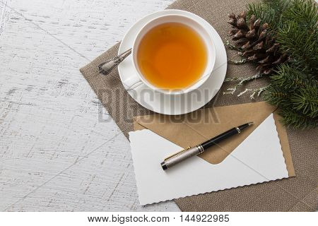 White cup of tea with blank paper with pen and Christmas decoration