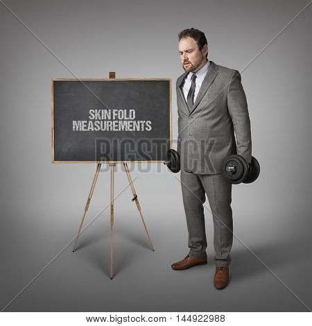 Skin fold measurements text on blackboard with businesssman holding weights