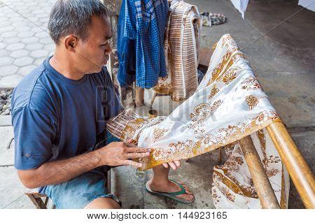 Yogyakarta, Indonesia - August 28, 2008: Man Painting Wax At Batik Factory