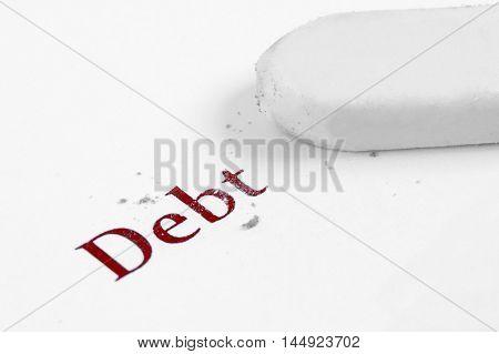 close up of word debt inscribed on white paper half erased with eraser